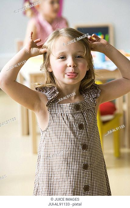 Preschool girl making face in classroom