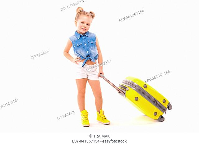 Isolated on white, cute little caucasian blonde girl in blue shirt, white shorts, sunglasses and yellow boots hold yellow suitcase by the handle, hand on waist