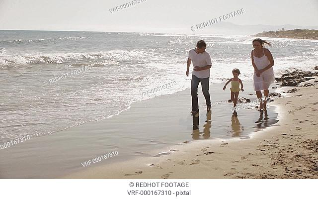 Panning shot of parents and daughter running on beach, Marbella region, Spain