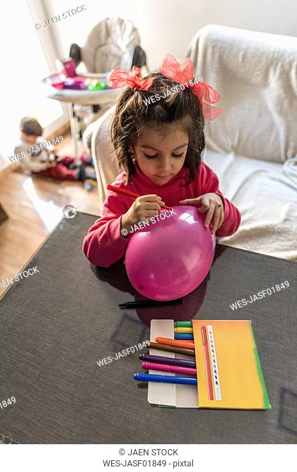 Little girl painting balloon, her little brother in the background
