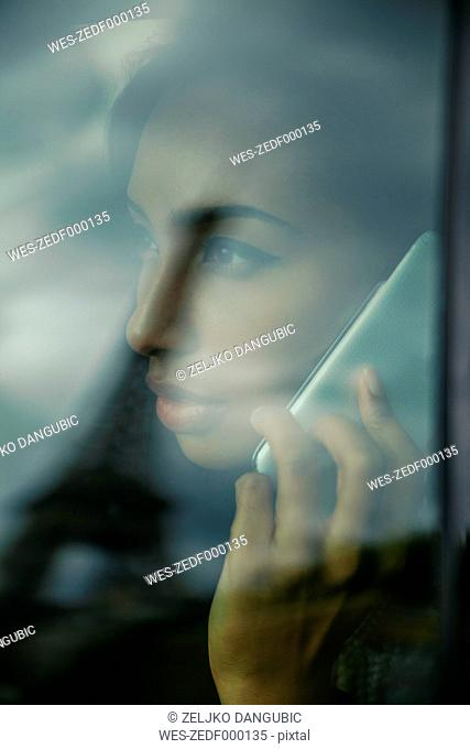 France, Paris, young woman looking through car window while telephoning