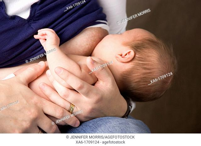 A woman holds her baby as she breastfeeds