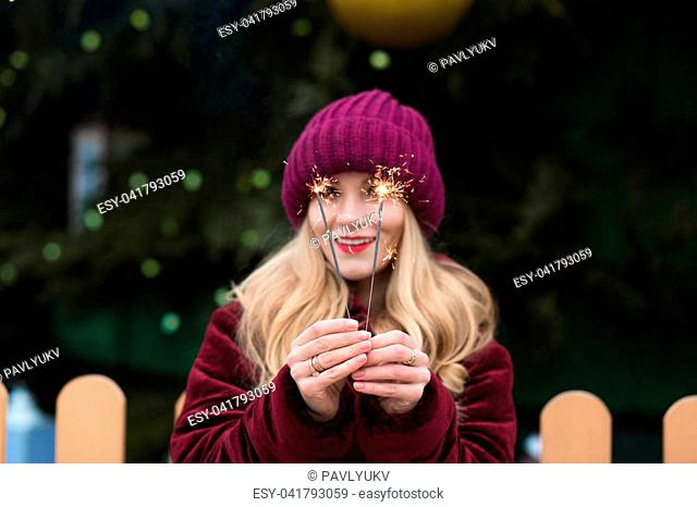 Funny young woman holding glowing Bengal lights at the main Christmas tree in Kyiv. Blur effect