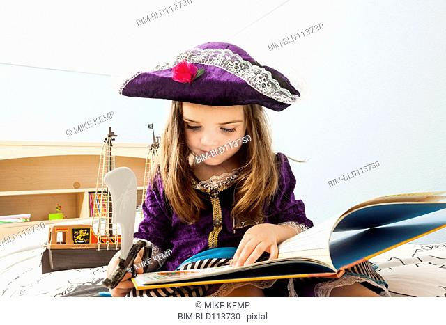 Caucasian girl reading book on bed