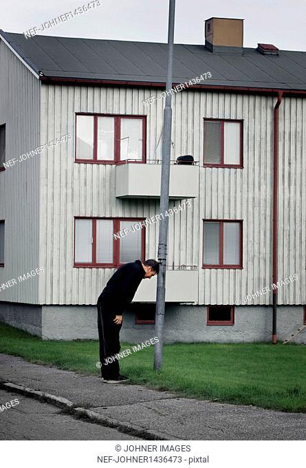 Man leaning at lamp post