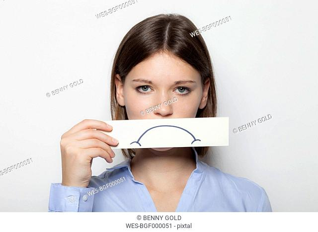 Young woman covering part of face with painted sad mouth