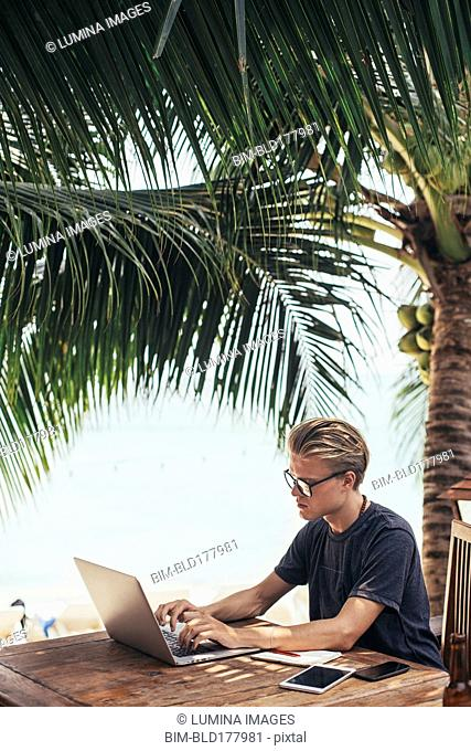 Caucasian man using laptop outdoors