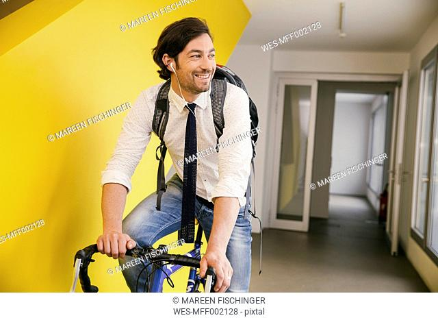 Portrait of smiling man with racing bicycle in a corridor
