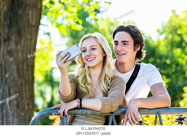 A young couple stands together at a bike rack on the university campus taking a self-portrait with a smart phone; Edmonton, Alberta, Canada