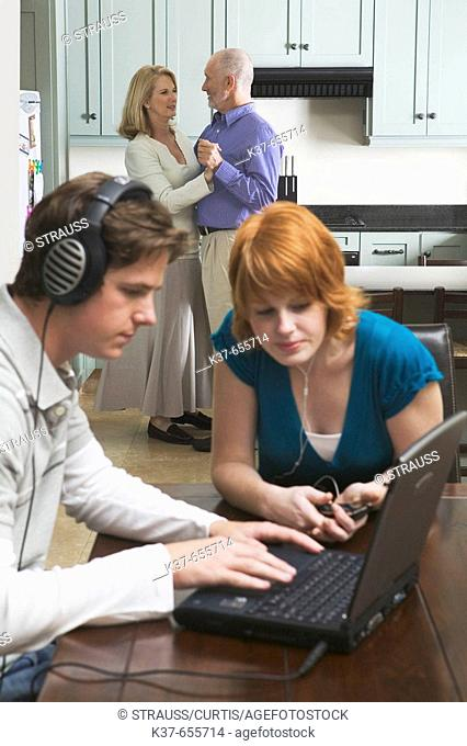 50-60 y/o couple dancing to music from stereo/radio in kitchen with teen/adult children sitting in dining room listening to music on laptop & ipod