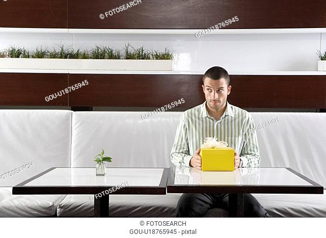 Man with present waiting in restaurant