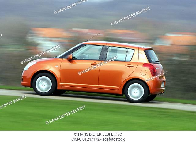 Car, Suzuki Swift 1.3, model year 2005-, orange , Limousine, small approx., driving, side view, country road