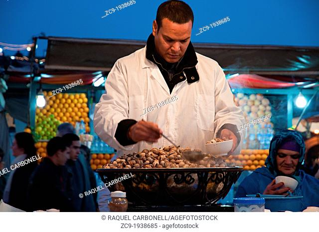 Man serving snails in his food street stall in Djemaa el Fna, Marrakech medina, Morocco