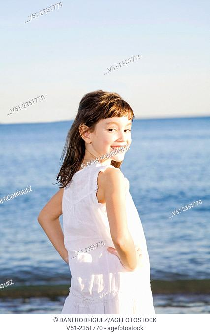 Portrait of a young girl at the beach smiling at camera