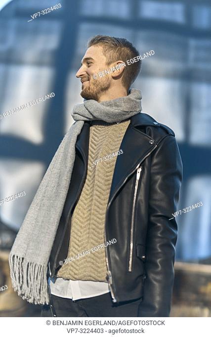 stylish man in winter clothing scarf looking sideways, in Munich, Bavaria, Germany