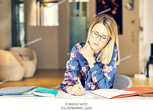 Businesswoman doing paperwork at desk
