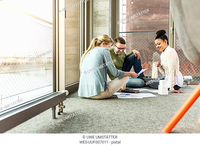 Three colleagues in office sitting on floor working together