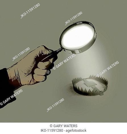 Hand holding magnifying glass over bear trap