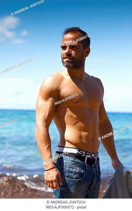 Greece, Ionic Islands, Corfu, shirtless man enjoying sunlight in front of the sea