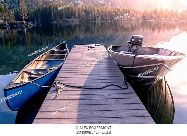 Canoe and motor boat moored at wooden pier on Echo Lake, High Sierras, California, USA