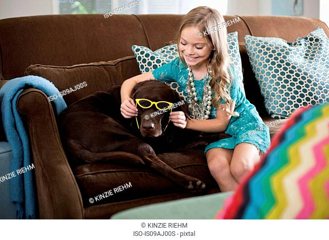 Girl holding sunglasses on reluctant chocolate colored labrador dog