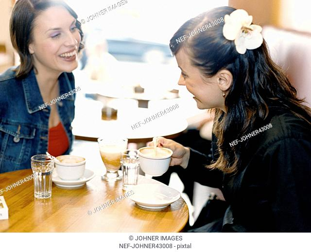 Women hang out and sit at a table and have coffee