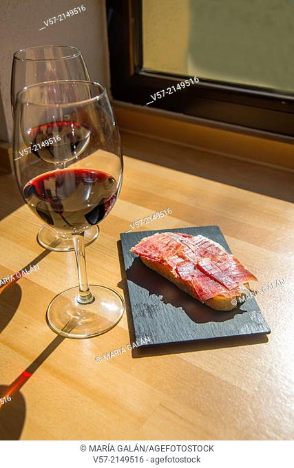 Spanish aperitif: two glasses of red wine and Iberian ham on toast