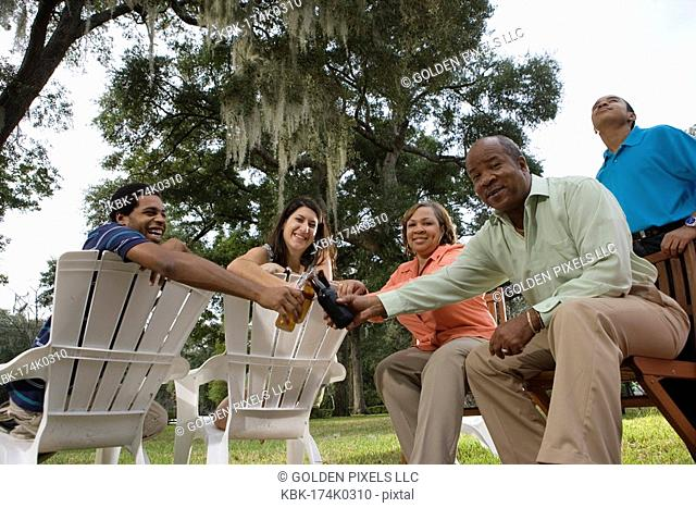 Mature couple with their son toasting drinks with inter-racial couple while sitting on lawn chairs