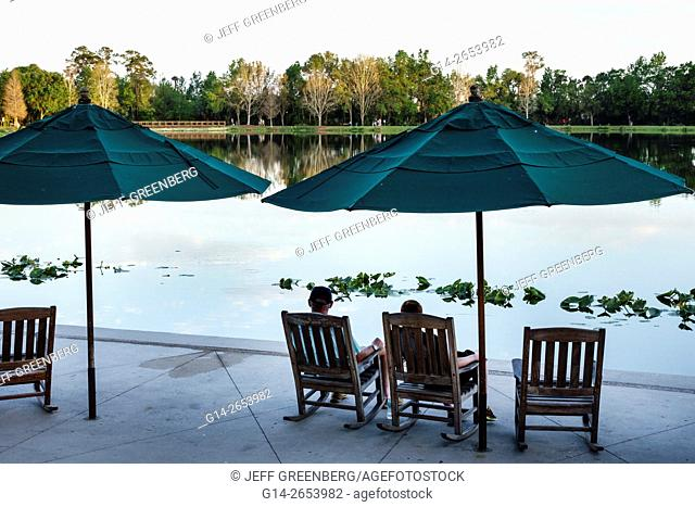 Florida, Orlando, Celebration, master-planned community, neo-urbanism, downtown, Front Street, Lake Rianhard, rocking chairs, umbrellas, scenery, water, couple