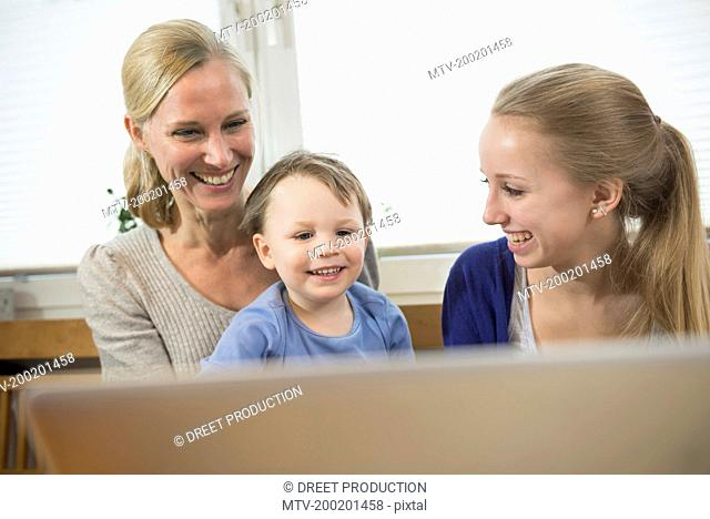 Mother, daughter and son being amused by something in internet