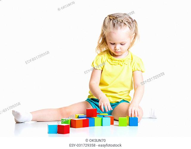kid girl 3 years old playing wooden cubes isolated on white