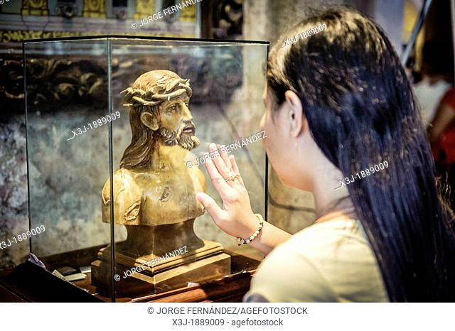 Woman praying in front of an statue of Christ inside The Basilica Minore del Santo Niño, Cebu, Philippines