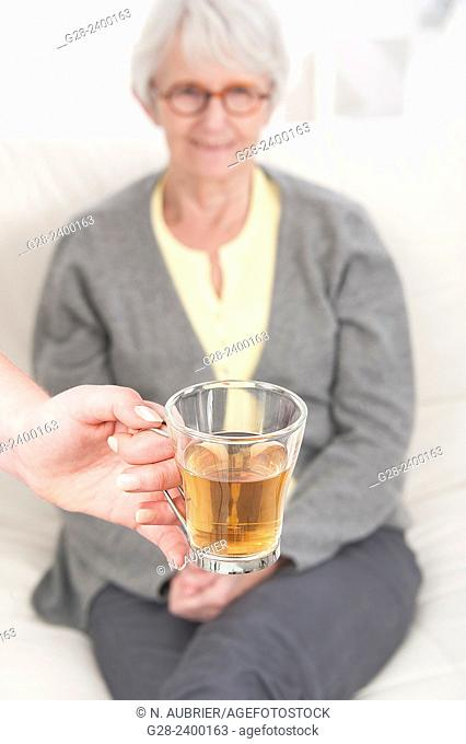 Young nurse or help or grand daughter holding a glass of tea, for patient or grandmother who is laughing in the background