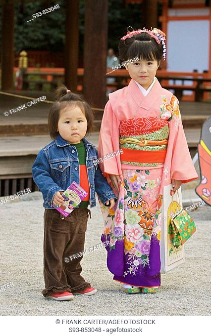 Two young sisters, one wearing a western jean jacket and the other wearing a traditional Japanese kimono posiing for a photo in the Shimogamo shrine in Kyoto