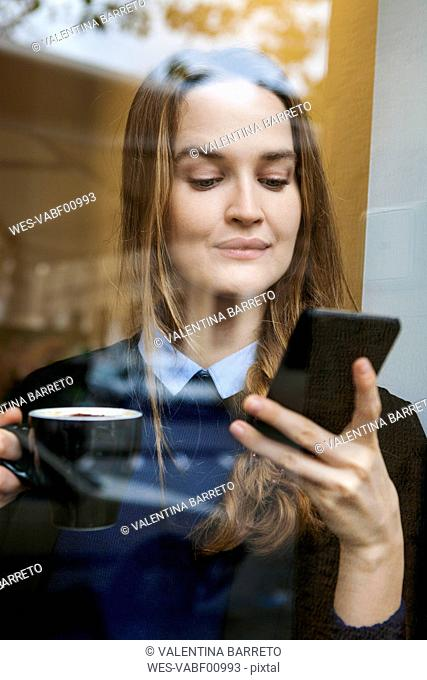 Smiling young woman in coffee shop with cup of coffee looking at smartphone