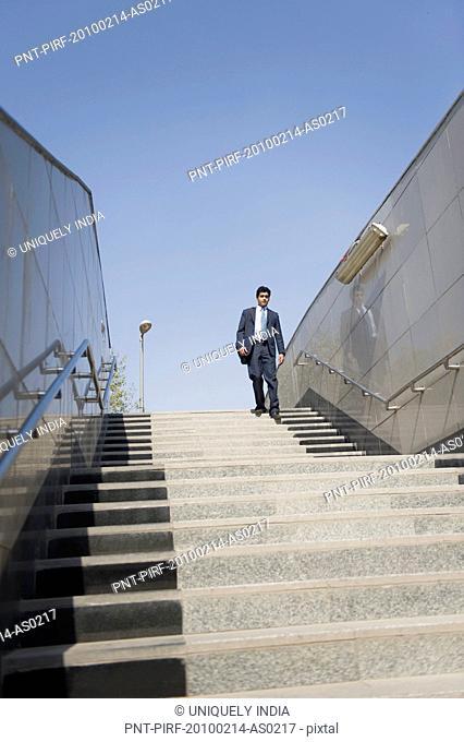 Businessman moving down stairs of a subway, Gurgaon, Haryana, India