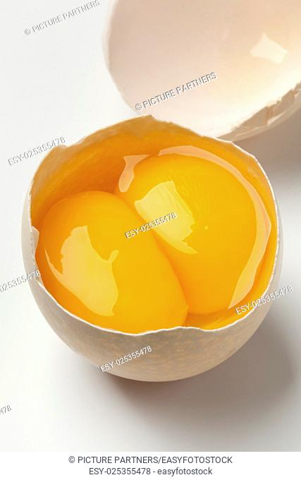 Broken raw fresh double yolk egg close up on white background