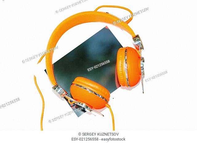 White tablet computer with orange headphones isolated on white