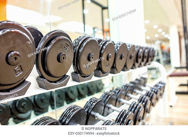Black dumbbell in fitness center room for background