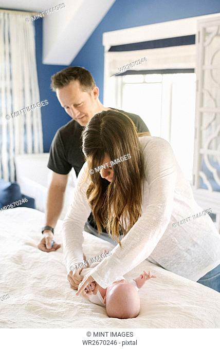 Two parents, mother and father at the changing table, changing a baby's diaper