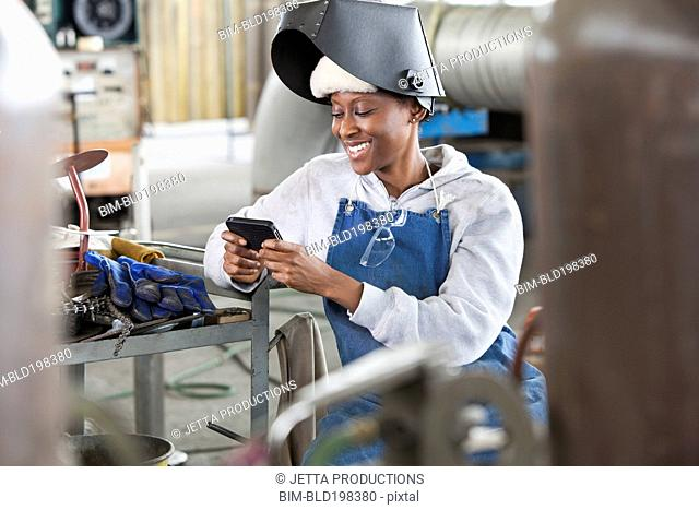 Black welder text messaging on cell phone on factory