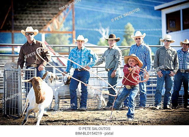 Cowboys teaching boy to lasso goat at rodeo