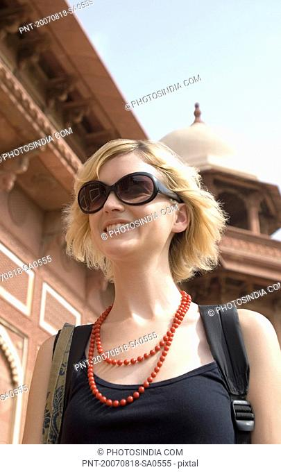 Close-up of a young woman smiling in front of a mausoleum, Taj Mahal, Agra, Uttar Pradesh, India