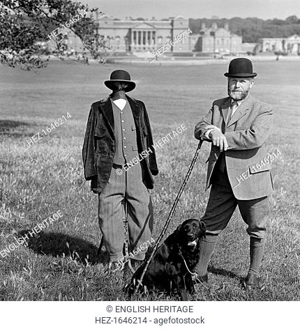 Man in breeches with a dog and a mannequin, Holkham Hall, Norfolk, 1978-1981.A man in breeches and a bowler hat standing beside a dummy dressed in a similar...
