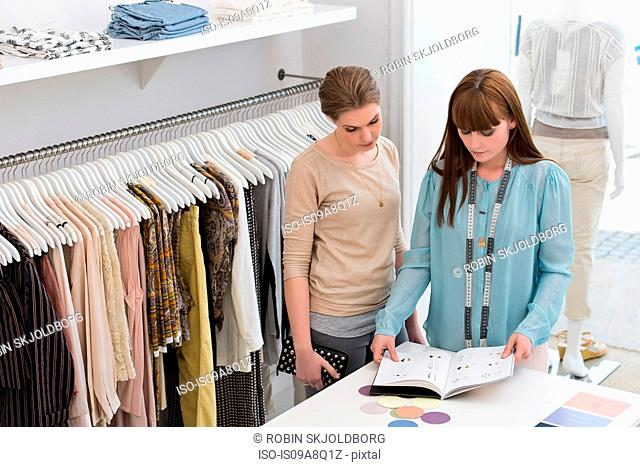 Two women in fashion boutique looking at designs