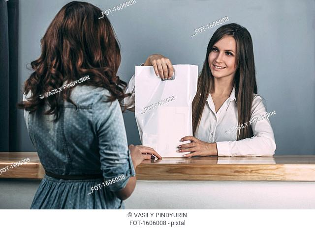 Young saleswoman handing over bag to female customer in store