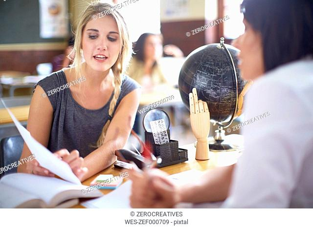 Student talking to teacher at desk