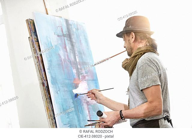 Male artist painting at easel in art studio