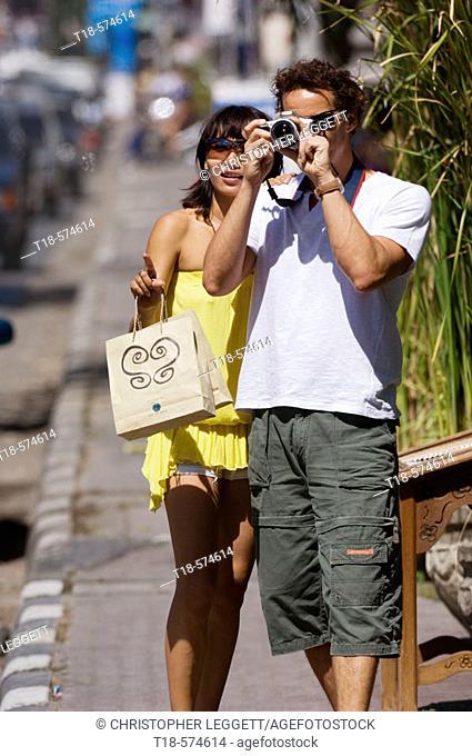 couple taking snapshot on sidewalk