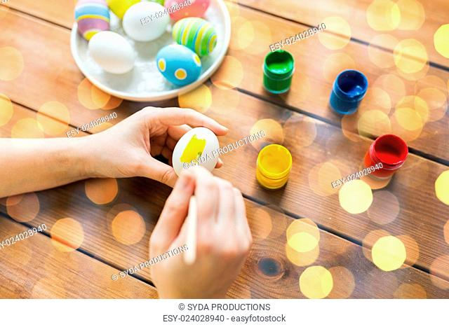 easter, holidays, tradition and people concept - close up of woman hands coloring easter eggs with colors and brush over lights
